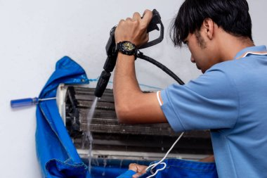 Men worker cleaning electrician air conditioner dirty in home