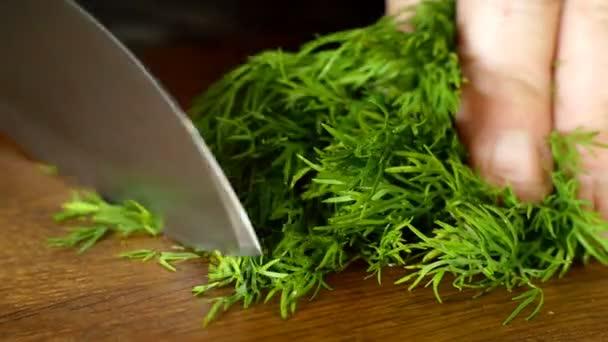 Šéfkuchař jemně nakrájejte čerstvý šťavnatý kopr kuchyňským nožem na dřevěnou řezací desku. Detailní záběr.