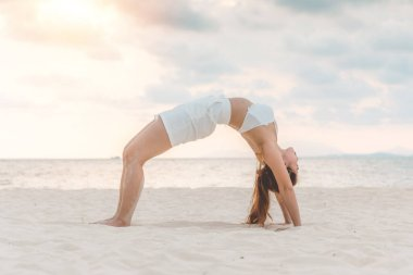 Asian young woman practice Yoga bridge Pose on the sand and beach with sunset beautiful sea in Tropical island,Feel comfortable and relax in holiday,Vacation Yoga Concept