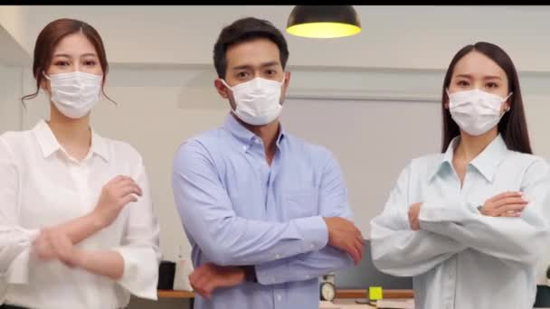 Asian indian business people standing wearing masks smile cross arm confidence with Business team at Co-Working space Due Covid-19 flu pandemic and protection,Small Business Startup Concept
