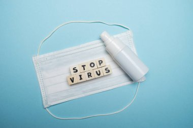 Hygienic face mask and white bottle hand sanitizer with stop virus word written on wood block isolated over blue background. Virus outbreak prevention concept.