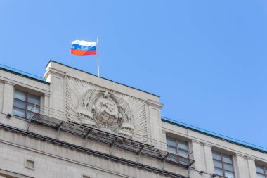 Russian National flag on top of the State Duma building, also known as Gosduma. Soviet coat of arms on the wall of building. Clear blue sky.