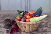 Composition of fresh vegetables in a basket on a wooden background. Autumn harvest. Happy Thanksgiving.