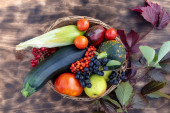 Composition of fresh vegetables in a basket on a wooden background. Autumn harvest. Happy Thanksgiving. Top view.
