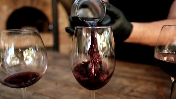 Slow motion of hands wearing black rubber gloves pouring red wine from a pitcher into a glass. 2 other glasses half full are visible.