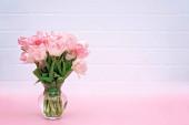 Frühlingsblumenstrauß aus rosa Tulpen in einer Vase an einer weißen Ziegelwand zum Muttertag, Geburtstag, Ostern, Frauentag. Kopierraum. Weiche selektive Fokussierung.