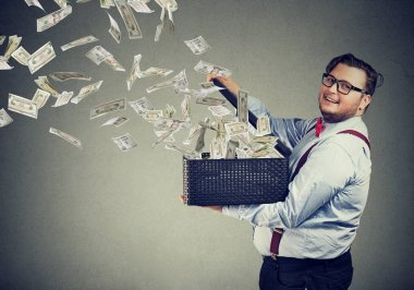 Excited business man in glasses opening a box letting dollar banknotes to fly away spreading the wealth