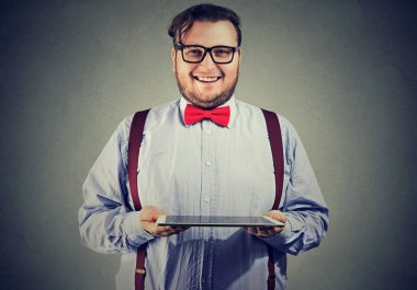 Stylish chunky man in bow tie showing tablet happily smiling at camera on gray background