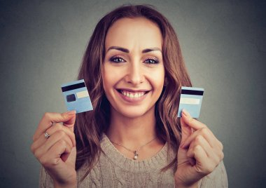 Beautiful young woman holding credit card cut into halves and looking happy debt payout
