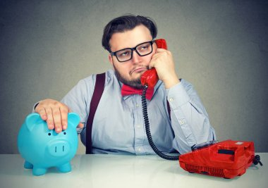 Chubby business man sitting with piggybank at table and having dull phone conversation looking annoyed