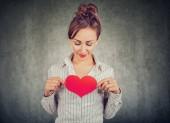 Hezká žena v košili drží velké červené srdce na prsou plný skvělé pocity na šedém pozadí