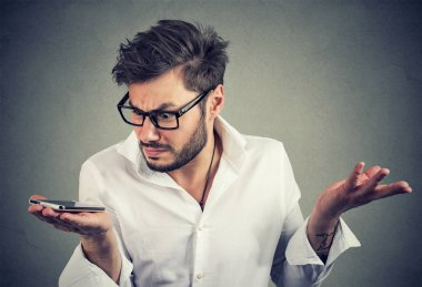Young trendy man holding phone and looking at it with frustration having problems with gadget