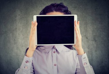 Anonymous brunette woman in shirt holding tablet in front of her face being incognito in social media on gray background