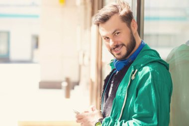 Young bearded man with blue headphones using smartphone on street looking at camera