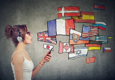 Young woman in headphones with smartphone learning different languages