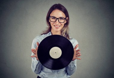 Young woman in glasses holding vintage vinyl record smiling at camera