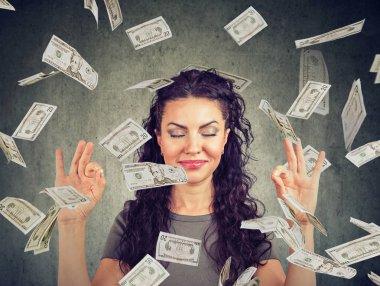 Happy business woman meditating under money rain