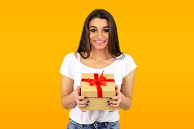 Portrait of a cute smiling girl holding a gift box looking at camera isolated on yellow background stock vector