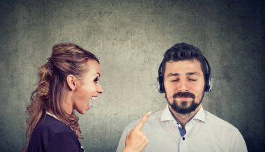 Angry woman yelling at a calm husband listening to music