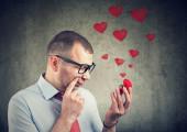 zamyšlený mladík se dívá na zásnubní prsten a má pochybnosti