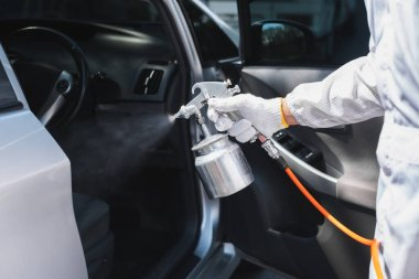 Close up hand of specialist cleaner wearing personal protective equipment PPE using chemical alcohol spray cleaning inside car to disinfect and decontaminate coronavirus covid-19 stock vector