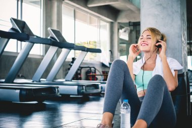 woman listening to music during workout and take a rest at sport gym for relaxation with happy and smile