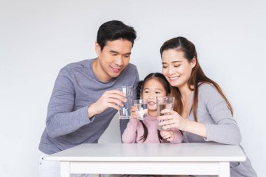 Happy Asian family drinking fresh water for heathly concept