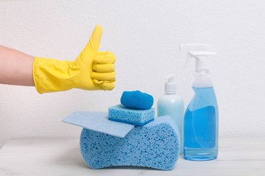 Sponges, rags, detergents on a gray table against the background of a white wall. The guy in the yellow glove takes a spray for cleaning.