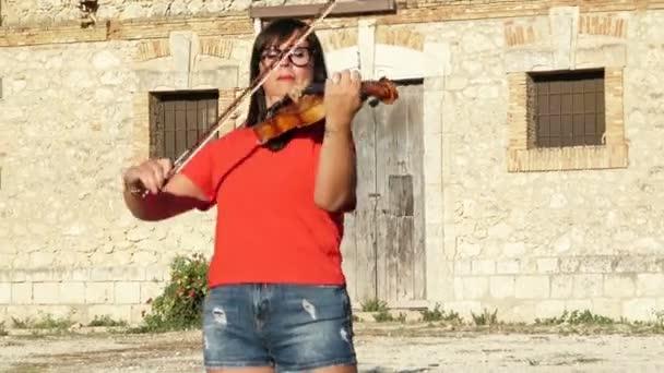 Nő játszik hegedű a szabadban. Piros ruha. Egy klasszikus hangszer zenekar. Klasszikus zene, mint a lelki gondozás.