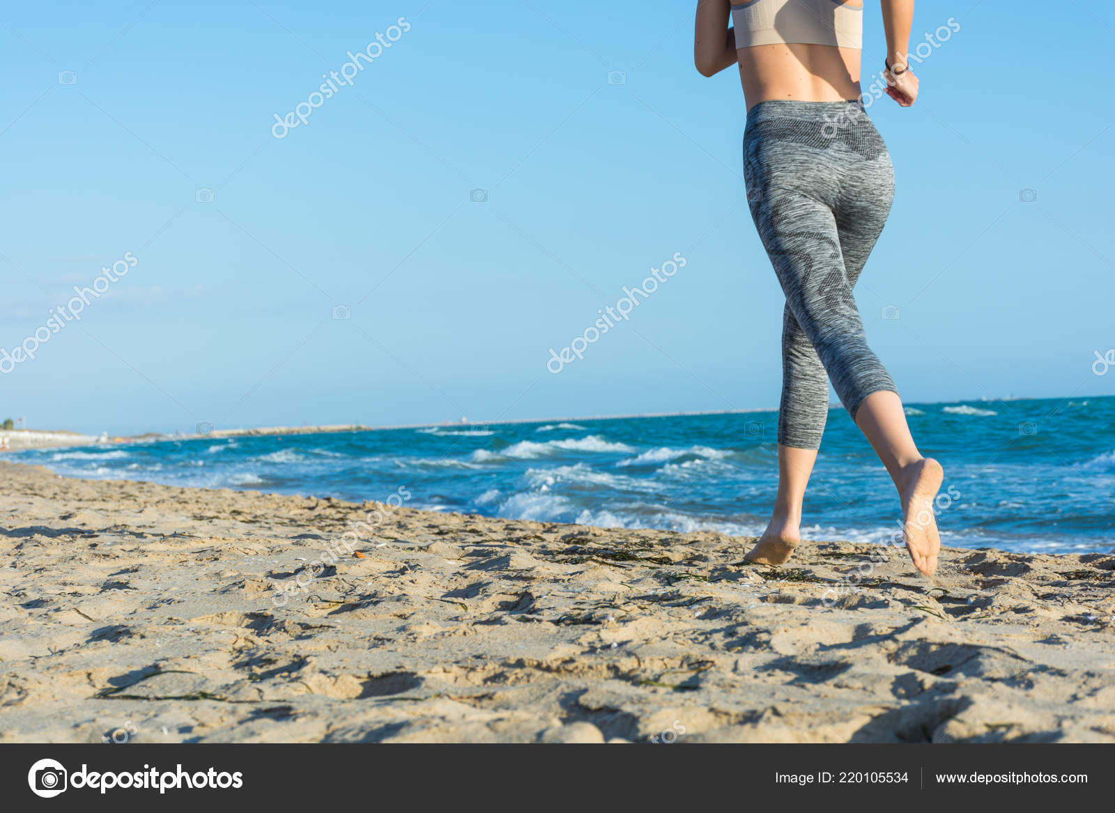 Girl runs on beach at sunset. Barefoot. It keeps fit and tanning on vacation.