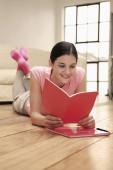 Frau liegt vorwärts auf dem Boden und liest Buch