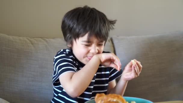 Healthy kid boy tasting sliced lime or lemon with funny face while having breakfast.