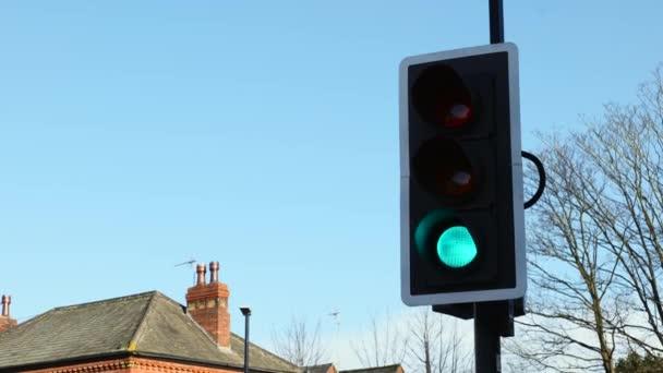 Britische Ampeln schalten an einem klaren, sonnigen Tag vor strahlend blauem Himmel von Grün auf Rot
