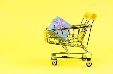 Small gift box in a shopping trolley on a yellow background. Holiday gifts