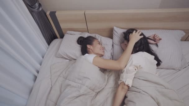 Two female lesbian couple lie on bed, looking each other eyes, playing each other head, LGBTQI, Pride Event, bonding relationship, comfortable bedroom and warm blanket, happiness before going to sleep