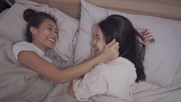 Asijské dvě ženy lesbičky pár mazlit uvnitř deky, držet ruce objetí líbání, přítelkyně úsměv smích, LGBTQ hrdost šťastný vztah, homosexuální společnost koncept, kamera nad záběr vysoký úhel pohledu