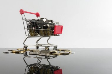 Trolley and coins isolated on white with reflection. Sales and shopping concept