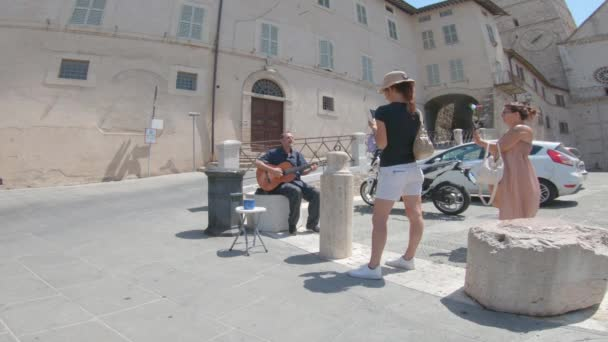 assisi,italy july 11 2020 :man playing and asking for an offer in front of the church