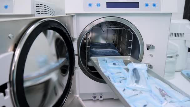 Labortechniker füllen Autoklaven mit zahnärztlichen Werkzeugen für die Sterilisation