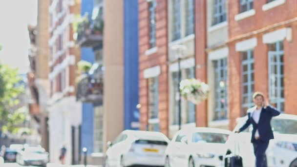 Geschäftsmann mit Mobile Phone Kreuzung Stadtstraße mit Koffer In Zeitlupe