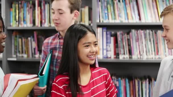Ruční záběr studentů středních škol s přáteli v knihovně