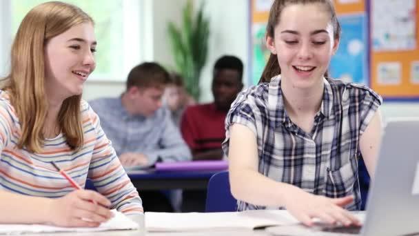 Két nő középiskolás diákok dolgozik a Laptop az osztályteremben