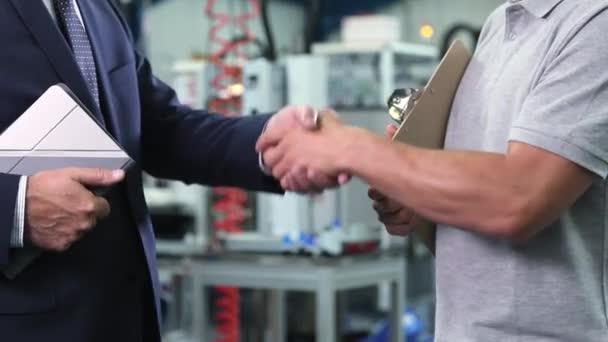 Detailní záběr podnikání vlastníka v továrně potřásl rukou s inženýr