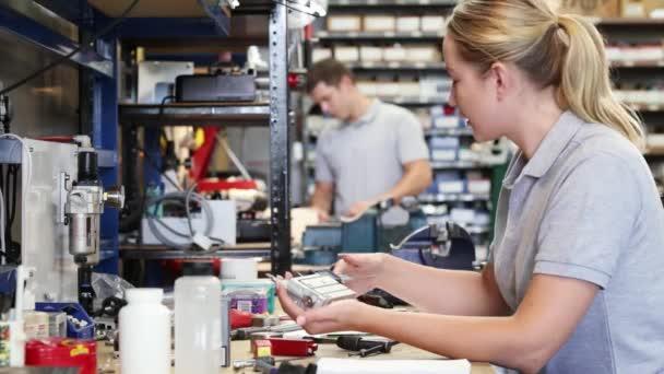 Inženýr pomáhá ženské učeň v továrně k měření komponenty pomocí mikrometru