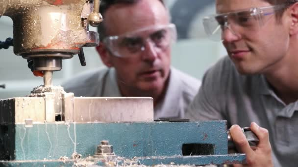 Pull-Fokusschuss eines Ingenieurs, der männliche Lehrlinge für den Einsatz von Bohrern in Fabrik ausbildet