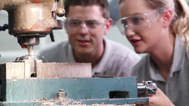 Pull-Fokusschuss eines Ingenieurs, der weibliche Lehrlinge für Bohrmaschinen in der Fabrik ausbildet