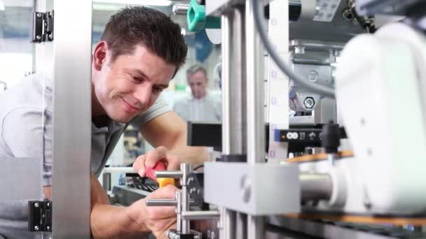 Inženýr s úpravou šroubovák automatizovaný stroj v továrně