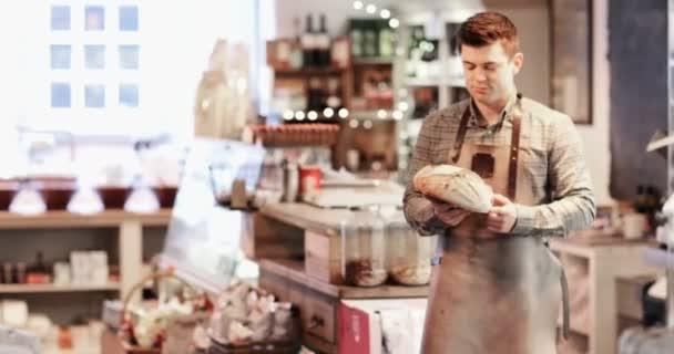 Portrait Of Smiling männlichen Eigentümer der Delikatessenladen trägt Schürze mit Brot