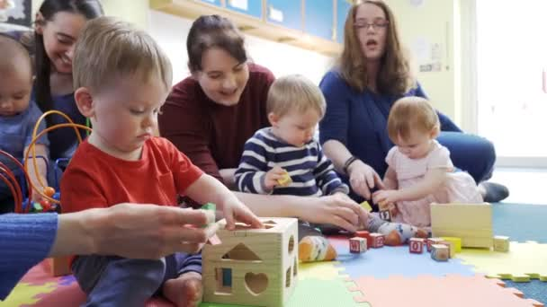 Group Of Mothers And Toddlers Playing With Toys At Playgroup
