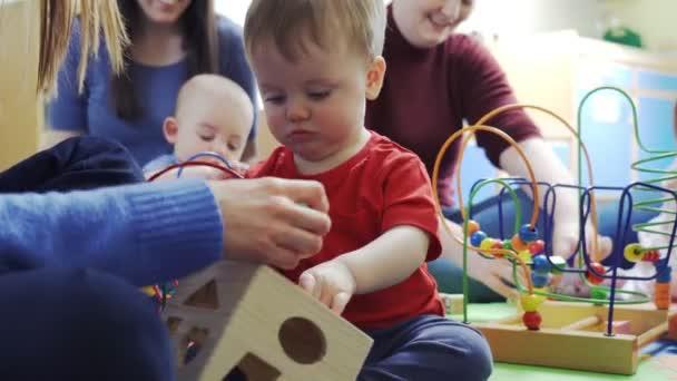 Skupina matek a batolat s hračkami v Playgroup